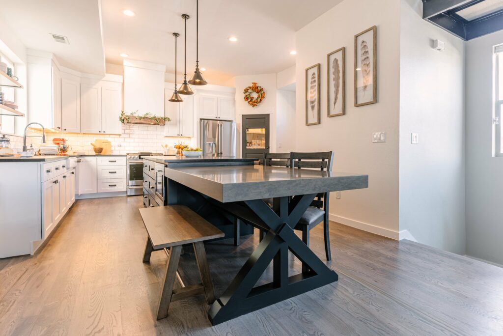 Remodeled kitchen with white cabinets and custom table
