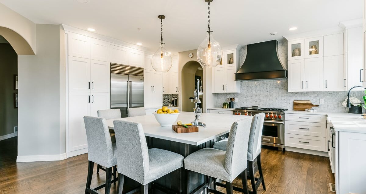 Bright kitchen with white cabinets and island with grey chairs